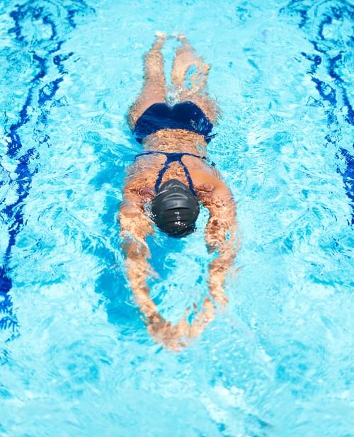 Uimari vatsallaan kädet edessä